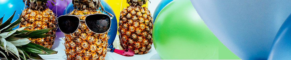Pineapple with sunglasses on surrounded by balloons